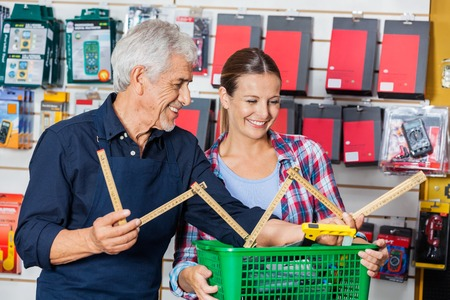hardware: Worker Showing Folding Ruler To Customer In Hardware Shop Stock Photo