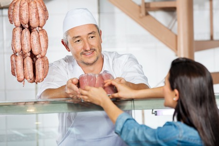 Butcher Giving Pack Of Sausages To Customer photo