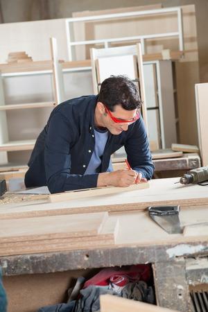 carpintero: Carpintero de medici�n Madera En Workbench Foto de archivo