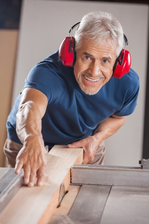 woodworking: Portrait Of Carpenter Cutting Wood With Tablesaw Stock Photo
