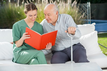 caretaker: Senior Man Reading Book With Female Caretaker On Couch Stock Photo