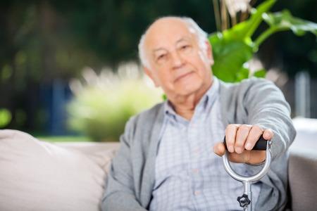 cane sofa: Portrait Of Senior Man Holding Metal Cane
