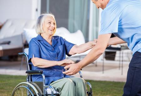Caretaker die Hogere Vrouw helpt om op te staan vanuit rolstoel