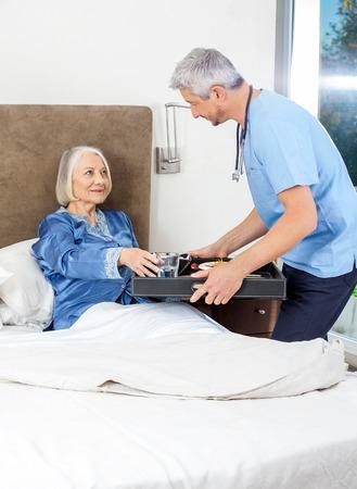 Caretaker Serving Breakfast To Senior Woman On Bed photo