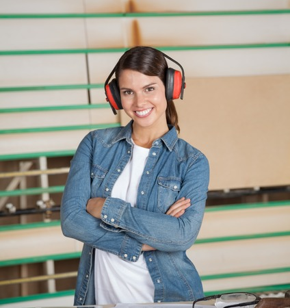 earmuffs: Confident Carpenter Wearing Ear Protectors In Workshop