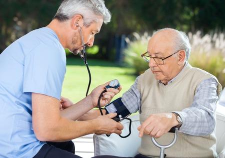 Dottore Misurazione pressione sanguigna Of Senior Man