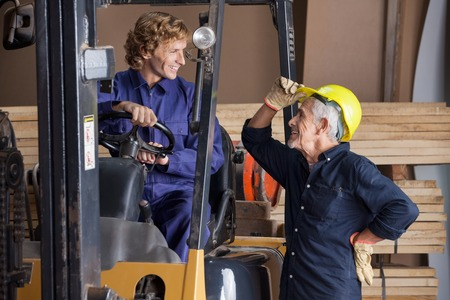 colleague: Carpenter Communicating With Colleague Using Forklift