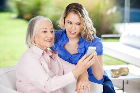 granddaughter: Granddaughter Assisting Granddaughter In Using Smartphone