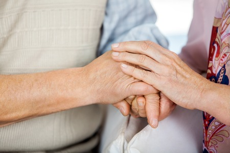 man holding woman: Senior Couple Holding Hands While Sitting On Chairs