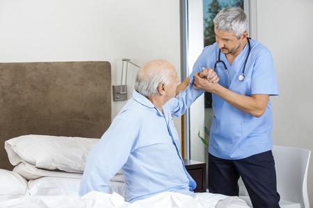 enfermera con paciente: Portero Hombre Ayudar hombre mayor Foto de archivo