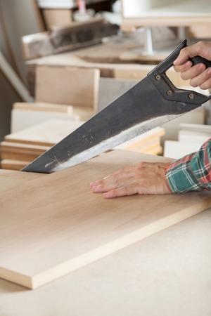 serrucho: Imagen recortada de carpintero de corte de madera con serrucho