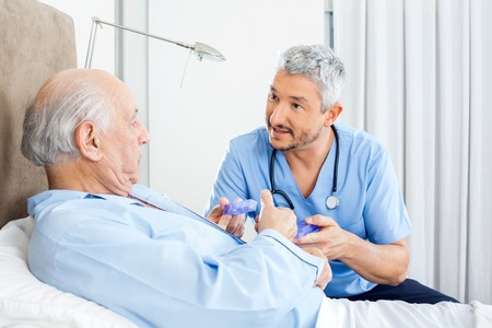happy patient: Caretaker Explaining Prescription To Senior Man Stock Photo