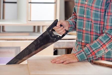 serrucho: Carpintero de cortar madera con serrucho Foto de archivo