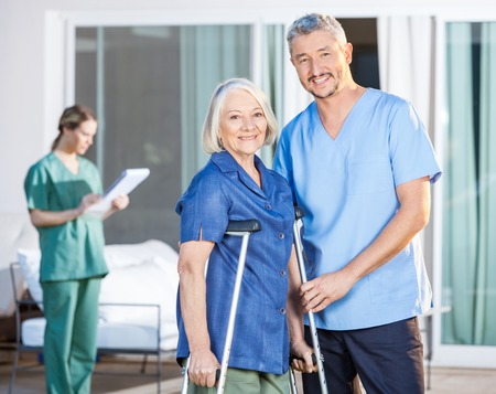 hospice: Happy Male Caretaker And Disabled Senior Woman Stock Photo