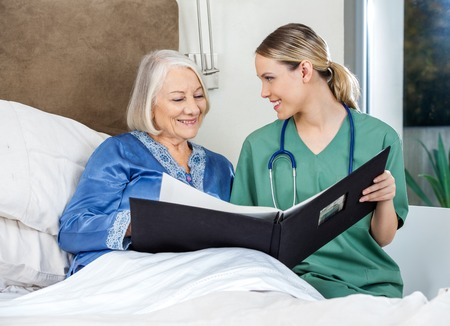 hospice: Caregiver Showing Medical Reports To Senior Woman