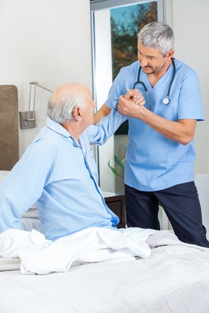 get up: Caretaker Supporting Senior Man To Get Up From Bed