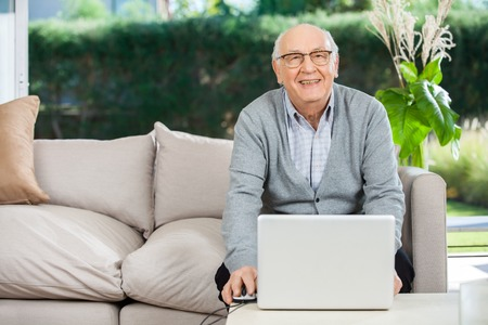 mobility nursing: Smiling Senior Man With Laptop At Nursing Home Porch