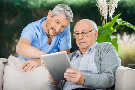 enfermeras: Portero Ayudar hombre mayor en Usando Tableta digital Foto de archivo