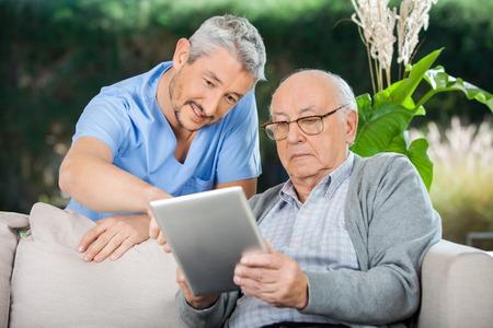 pielęgniarki: Stróż Wspomaganie starszy mężczyzna w Korzystanie z cyfrowym tablecie Zdjęcie Seryjne