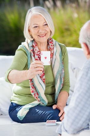 senior adult man: Smiling Senior Woman Playing Cards With Man