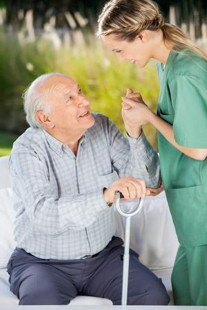 Custode Femminile Aiutare Senior Man Per alzarsi dal divano