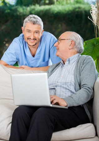 Caretaker With Senior Man Using Laptop On Couch photo