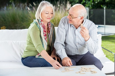 dominoes: Happy Senior Couple Playing Dominoes At Porch