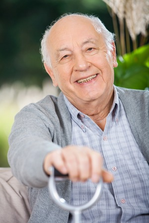 Portrait Of Smiling Senior Man Holding Walking Stick photo