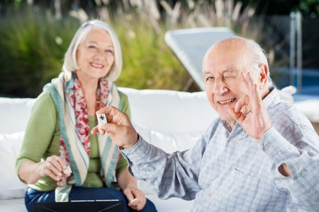 rummy: Senior Man Gesturing Okay While Playing Rummy With Woman
