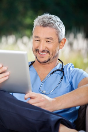 Male Nurse Smiling While Looking At Tablet Computer photo