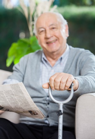 cane sofa: Happy Senior Man With Newspaper And Cane Sitting On Couch Stock Photo