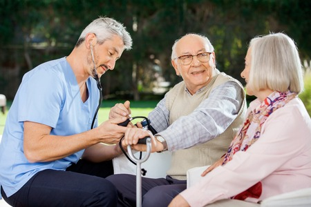 Doctor Measuring Blood Pressure Of Senior Man Sitting Beside Wom