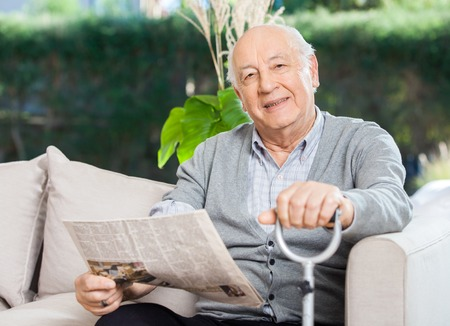 cane sofa: Senior Man With Newspaper And Stick Sitting On Couch