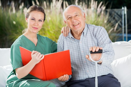 home care: Confident Female Nurse And Senior Man With Book Stock Photo