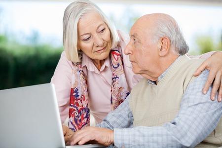 haushaltshilfe: �ltere Paare, die einander betrachten W�hrend Laptop benutzen