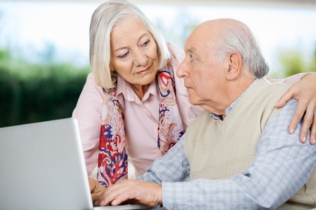 home care: Senior Couple Looking At Each Other While Using Laptop