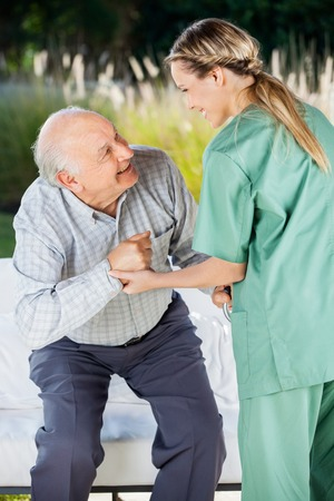 residents: Female Nurse Helping Senior Man To Sit On Couch