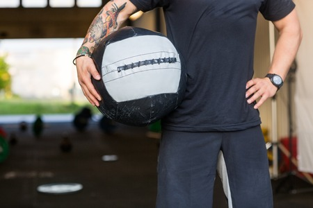 exercise ball: Fit Man Carrying Medicine Ball Stock Photo