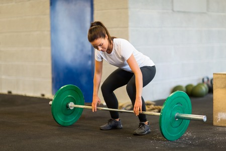 weightlifting equipment: Woman Lifting Barbell At Gym