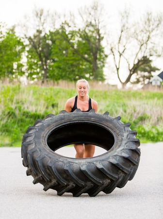 flipping: Athlete Doing Tire-Flip Exercise On Street
