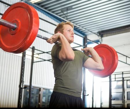levantamiento de pesas: Barbell de elevaci�n del hombre en la gimnasia Foto de archivo