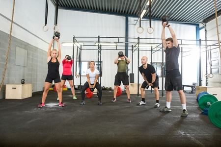 group: Athletes Lifting Kettlebells in Cross Fitness Box