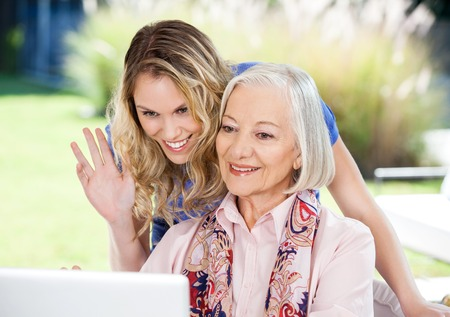 Happy Senior Woman And Granddaughter Video Chatting On Laptop photo