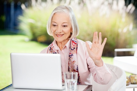 care at home: Senior Woman Waving While Video Chatting On Laptop Stock Photo