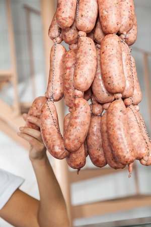 carnicer�a: Butcher Agarrados de salchichas en Carnicer�a Foto de archivo