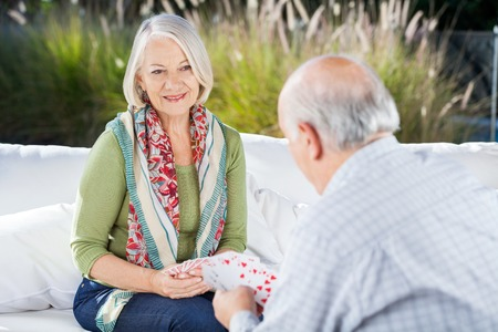 nursing care: Happy Senior Woman Playing Cards With Man