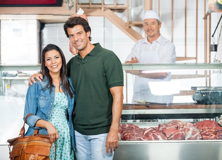 Happy Couple Standing In Butchery photo