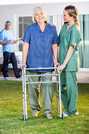 ancianos caminando: Enfermera asiste a la mujer mayor a recorrer con el capítulo Zimmer Foto de archivo