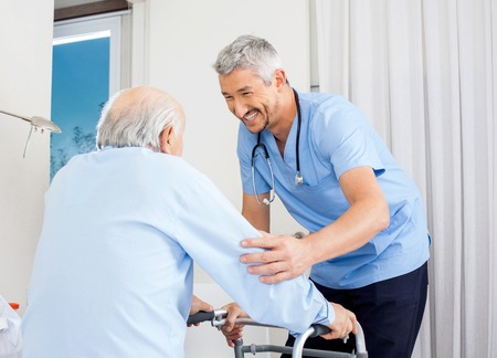 happy patient: Caretaker Helping Senior Man To Use Walking Frame Stock Photo
