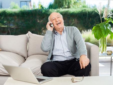 answering: Cheerful Senior Man Answering Smartphone At Porch